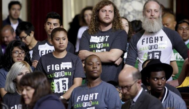 People stand as the Los Angeles City Council prepares to vote on a proposal to raise the minimum wage to $15.00 per hour in Los Angeles, California